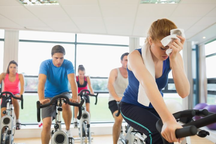 Determined and tired people working out at an exercise bike class